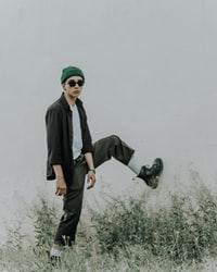 man in black jacket and brown pants standing on green grass field 身穿黑色夹克和棕色裤子的男子站在绿草地上