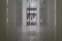 people walking on hallway inside building 人们在大楼内的走廊上行走