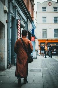 man in brown coat walking on sidewalk during daytime 白天穿棕色外套走在人行道上的男人