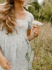 woman in white floral dress holding white flower 身穿白色花裙的女子手持白花