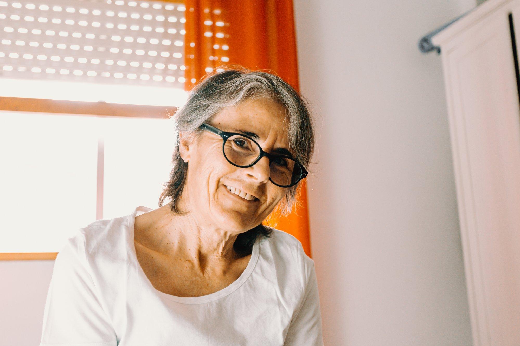 woman smiling to the camera with orange curtains behind 女人对着镜头微笑,身后是橙色的窗帘。