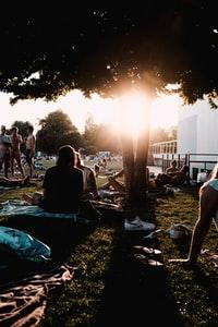 people sitting on green grass field during sunset 日落时人们坐在青草地上