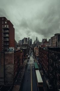 cars on road between high rise buildings under white clouds during daytime 白天白云下高楼之间道路上的汽车
