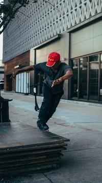 man in black jacket and red helmet walking on sidewalk during daytime 白天穿着黑色夹克和红色头盔在人行道上行走的男子