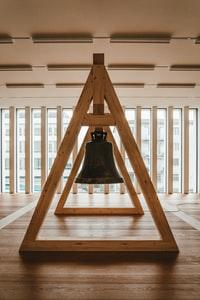 black bell on brown wooden stand 棕色木架上的黑色钟