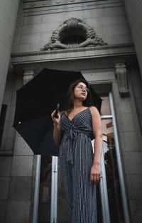 woman in black and white stripe dress holding umbrella